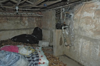 (Hoffman Confession Zachariah) A detective's photo showing the makeshift bed of leaves and blankets that Matthew Hoffman had in a dark and dank corner of his basement where he kept his teenage kidnap victim last November.